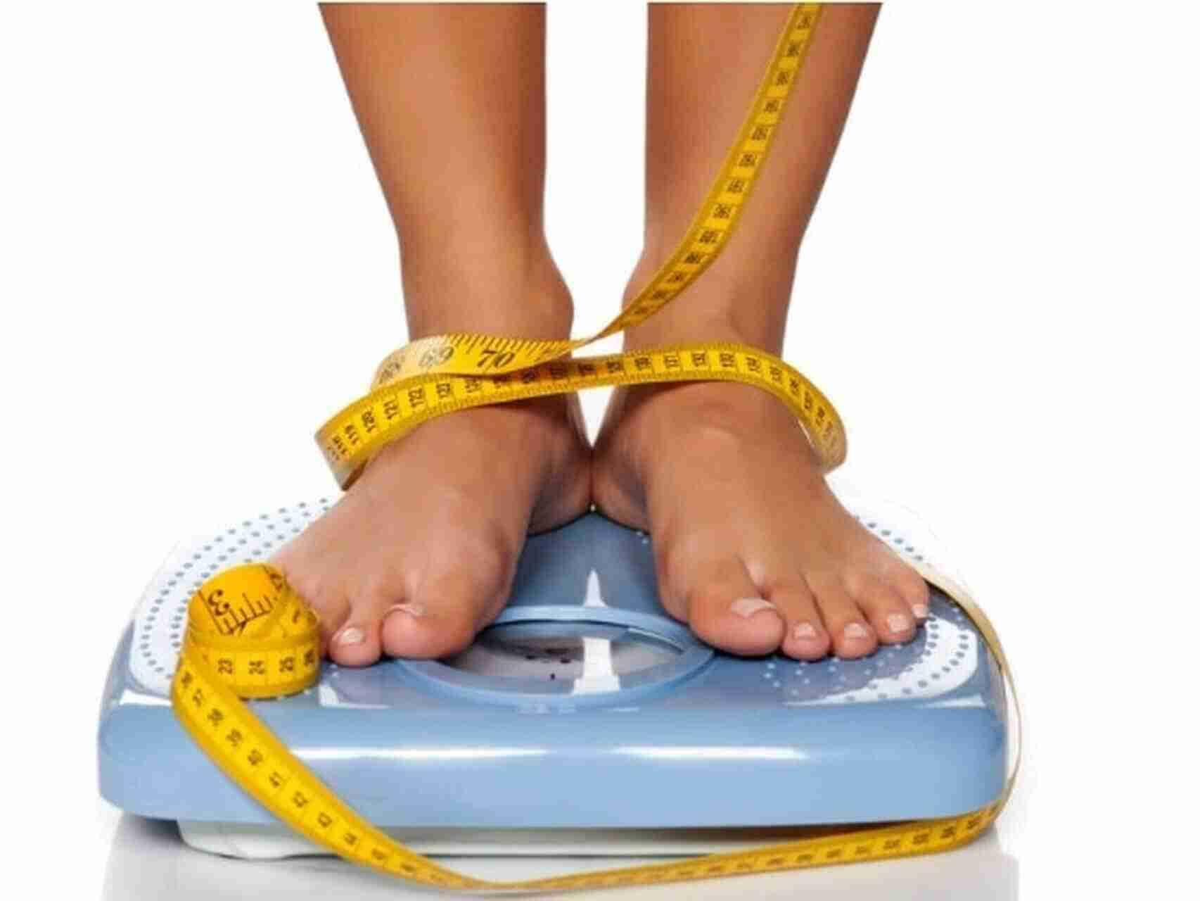 Piernas en una báscula junto con una cinta métrica tras visitar la consulta del nutricionista