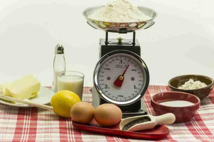 Mesa con una balanza encima para medir la equivalencia de los alimentos
